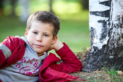Thoughtful boy in red jacket lying next to tree, looking at camera Royalty Free Stock Image