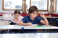 Thoughtful Boy Sitting At Desk Stock Photos