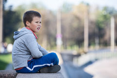 Thoughtful boy sitting on edge of granite plate, looks into the distance Stock Images