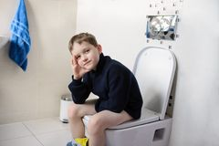 Thoughtful boy sitting on the toilet. Dressed in a dark navy blue woolen sweater stock photo