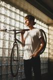 Thoughtful boy standing and holding bicycle that leaning on his shoulder dreamily looking aside. Young man in white t. Thoughtful boy standing and holding Stock Image