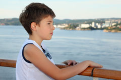Thoughtful boy stands on board of ship Royalty Free Stock Images