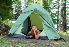Thoughtful boy in tent Stock Photo