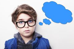 Thoughtful young boy wearing glasses with an empty thought bubble. Thoughtful boy wearing glasses with an empty thought bubble Stock Photos