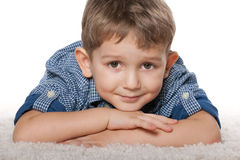 Thoughtful boy on the white carpet Stock Photography