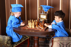 Thoughtful boys in blue suits play chess Royalty Free Stock Photos