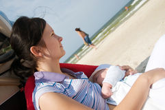 Thoughtful breast feeding. Thoughtful mother breast feeding her newborn on the beach stock photo