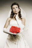 Thoughtful bride with bunch of flowers Stock Photos