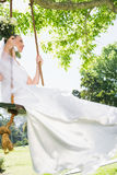 Thoughtful bride swinging in garden Royalty Free Stock Photos