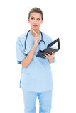 Thoughtful brown haired nurse in blue scrubs holding an agenda Royalty Free Stock Image