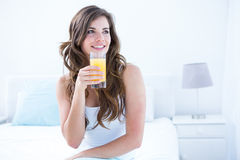 Thoughtful brunette drinking a glass of orange juice Royalty Free Stock Photography