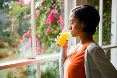 Thoughtful brunette drinking orange juice Stock Photo