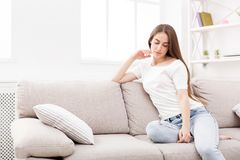 Pensive young woman at home stock image