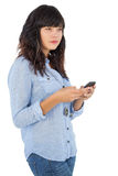 Thoughtful brunette with her mobile phone texting a message Stock Photography