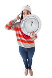 Thoughtful brunette holding a clock Royalty Free Stock Images