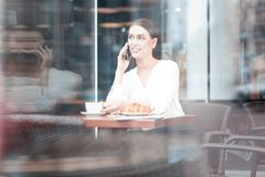 Thoughtful brunette listening her interlocutor. Playful glance. Pretty woman taking cup of tea and expressing positivity while sitting in cafe Royalty Free Stock Photography