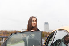 Thoughtful brunette standing at open door of taxi in city Royalty Free Stock Image