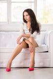 Thoughtful brunette wearing white dress stock photography