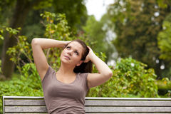 Thoughtful brunette woman. A thoughtful beautiful brunette woman in her twenties sitting on a bench in a park and looking at something Royalty Free Stock Images