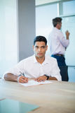 Thoughtful business executive writing on notebook in conference room Royalty Free Stock Photos