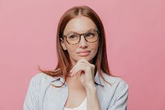 Thoughtful business lady holds chin, looks aside with pensive expression, wears spectacles, has dark hair, dressed in shirt,. Thinks on developing new strategy royalty free stock image