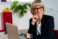 Thoughtful business lady seated in office Stock Image