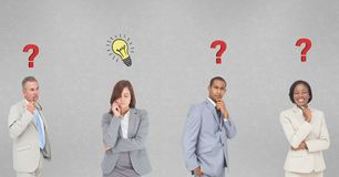 Thoughtful business people with question marks and light bulb marks on wall Royalty Free Stock Photography