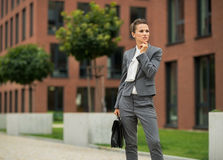 Thoughtful business woman with briefcase. In front of office building royalty free stock image