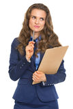 Thoughtful business woman with clipboard Stock Images