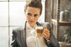 Thoughtful business woman drinking coffee Stock Photo