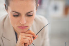 Thoughtful business woman with eyeglasses Royalty Free Stock Photography