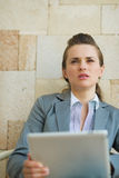 Thoughtful business woman holding tablet PC Stock Photo