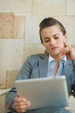 Thoughtful business woman looking in tablet PC Stock Photos
