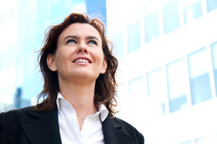 Thoughtful business woman looking up and smiling Stock Photo