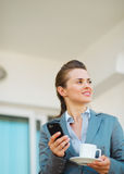 Thoughtful business woman with mobile phone. On terrace Stock Photography