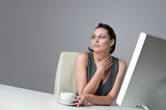 Thoughtful business woman at office with coffee. Thoughtful successful business woman at office having cup of coffee sitting at computer desk Stock Photo