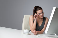 Thoughtful business woman at office with coffee. Thoughtful successful business woman at office having cup of coffee sitting at computer desk Royalty Free Stock Images