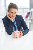 Thoughtful business woman with piggy bank royalty free stock photography