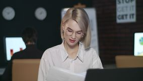 Thoughtful business woman reading document on laptop in dark office. Focused business woman looking financial reports in late office. Closeup girl working at stock video