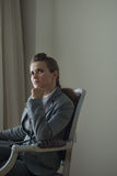 Thoughtful business woman sitting in chair in room. Thoughtful business woman sitting in chair in hotel room Royalty Free Stock Image