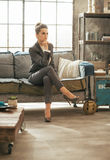 Thoughtful business woman sitting on divan in loft Stock Image
