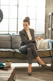 Thoughtful business woman sitting on divan in loft Stock Photo