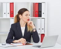 Thoughtful business woman sitting at office workplace looking into the distance. Royalty Free Stock Photography