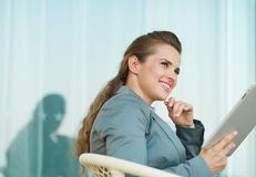 Thoughtful business woman using tablet PC Stock Images