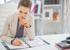 Thoughtful business woman working with documents Stock Photo