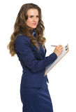 Thoughtful business woman writing in clipboard Stock Photography