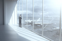 Thoughtful businessman in airport terminal. Interior with daylight and a view of airplanes outside. 3D Rendering Stock Photo