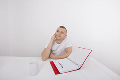 Thoughtful businessman answering smart phone at desk Royalty Free Stock Photos