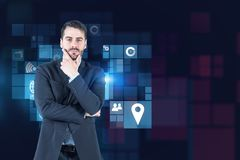Thoughtful businessman, business icons. Thoughtful bearded businessman in suit standing over dark blue background with business icons. Toned image royalty free stock images