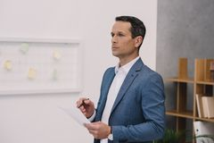 thoughtful businessman with business paper looking away stock photography